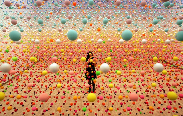 "Australian artist Nike Savvas makes final adjustments to her art piece consisting of over 50,000 polystyrene balls at the New South Wales Art Gallery in Sydney August 3, 2006. The sculpture titled ""Atomix – Full of Love, Full of Wonder"", vibrates with wind from 10 fans and represents the different ""shimmering"" colours in a hot, outback landscape. It is part of a sculpture exhibition ""Adventures with Form in Space"". (Photo by David Gray/Reuters)"