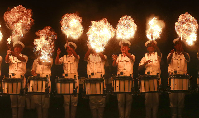 Members of the Indian Navy band perform a fire act during rehearsals for Naval Day celebrations in Mumbai, India, Wednesday December 2, 2015. India celebrates Navy Day on Dec. 4. (Photo by Rafiq Maqbool/AP Photo)