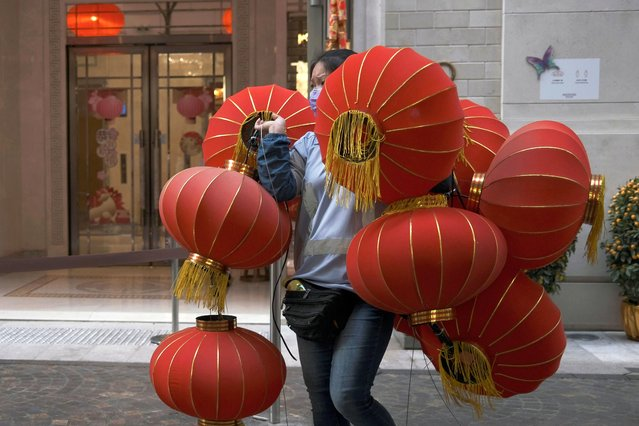 A worker wearing a face mask carries red lanterns, ahead of the Chinese Lunar New Year, following the coronavirus disease (COVID-19) outbreak, in Hong Kong, China on January 28, 2021. (Photo by Tyrone Siu/Reuters)