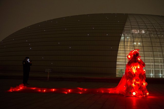 Performance artist Kong Ning wears a gown with glowing red light and stop signs to raise awareness of the smog enveloping Beijing, December 9, 2015. (Photo by Ng Han Guan/AP Photo)