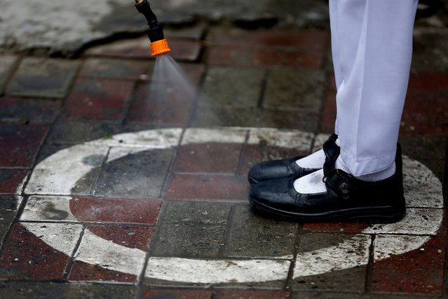 A worker sprays sanitizer on a student's shoes at a school in Lahore, Pakistan, Wednesday, Nov. 25, 2020. Pakistan will again close all educational institutions as of Thursday November 26 because of a steady and increasingly drastic increase in coronavirus cases. (Photo by K.M.Chaudary/AP Photo)
