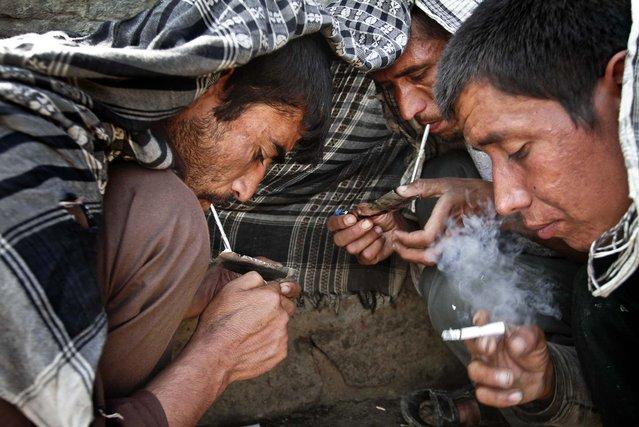 Drug addicts smoke heroin in Kabul, Afghanistan, on July 3, 2013. (Photo by Rahmat Gul/Associated Press)