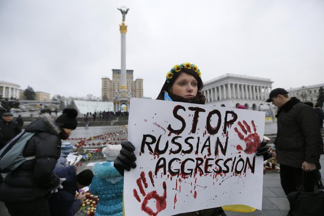 A woman holds a placard during a rally on Independence Square in Kiev, Ukraine, Sunday, January 25, 2015 in solidarity with the victims of a rocket attack on the coastal city of Mariupol. Indiscriminate rocket fire slammed into a market, schools, homes and shops Saturday in Ukraine's southeastern city of Mariupol. (Photo by Sergei Chuzavkov/AP Photo)