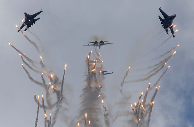 Su-27 jets of the Russian Knights release decoys as they perform aerial demonstrations during the International Maritime Defense show in St.Petersburg, Russia, on July 7, 2013. (Photo by Dmitry Lovetsky/Associated Press)