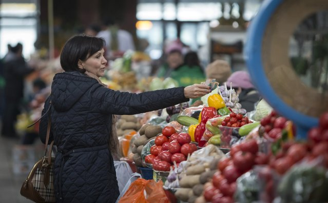 A customer hands over money to a vendor as she visits the Green Bazaar in Almaty January 23, 2015. (Photo by Shamil Zhumatov/Reuters)