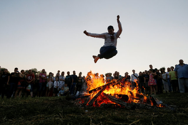 A man jumps over a campfire during a celebration on the traditional Ivana Kupala (Ivan the Bather) holiday in Kiev, Ukraine July 6, 2018. The ancient tradition, originating from pagan times, is marked with grand overnight festivities during which people sing and dance around campfires, believing it will purge them of their sins and make them healthier. (Photo by Valentyn Ogirenko/Reuters)