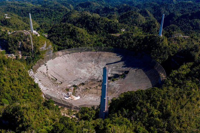 This aerial view shows the damage at the Arecibo Observatory after one of the main cables holding the receiver broke in Arecibo, Puerto Rico, on December 1, 2020. The radio telescope in Puerto Rico, which once starred in a James Bond film, collapsed Tuesday when its 900-ton receiver platform fell 450 feet (140 meters) and smashed onto the radio dish below. (Photo by Ricardo Arduengo/AFP Photo)