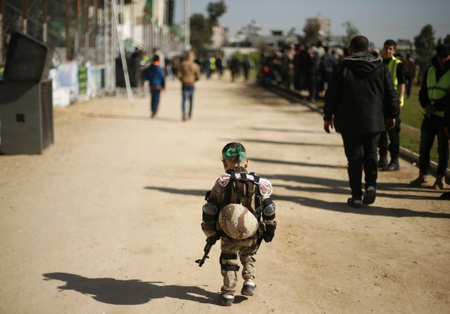 """A Palestinian boy wearing a military costume arrives at a military-style graduation ceremony for Palestinian youths who were trained at one of the Hamas-run Liberation Camps, in Gaza City January 29, 2015. Hamas's armed wing organized """"Liberation Youths Camps"""" for young Palestinians aged between 15 and 21 to prepare them to """"confront any possible Israeli attack"""", Hamas officials said. (Photo by Suhaib Salem/Reuters)"""