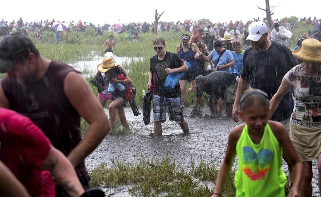 People walk back to solid ground as rain pours down at the annual Chincoteague Pony Swim, on Chincoteague Island. (Photo by Doug Mills/The New York Times)