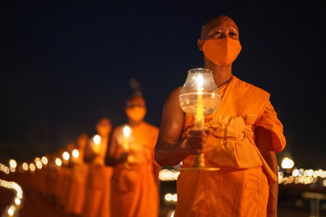 Buddhist monks hold candles during a ceremony to commemorate Makha Bucha Day at the Wat Phra Dhammakaya temple, in Pathum Thani province, Thailand, February 26, 2021. (Photo by Athit Perawongmetha/Reuters)
