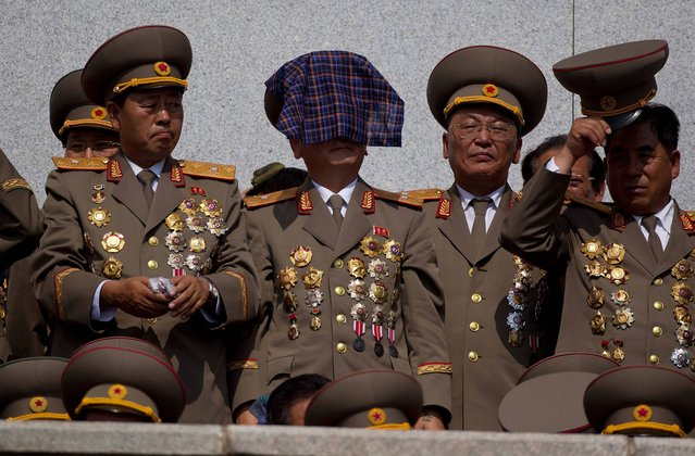 A North Korean military veteran uses a handkerchief to protect himself from the sun in the stands at a mass military parade on Kim Il Sung Square in Pyongyang to mark the 60th anniversary of the Korean War armistice in North Korea, Saturday, July 27, 2013. (Photo by David Guttenfelder/AP Photo)