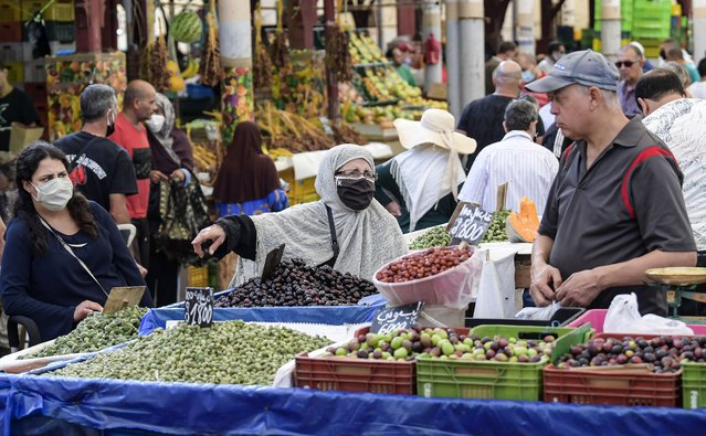 A mask-clad customer (COVID-19 coronavirus precaution) speaks with a fruit seller at his stall at the central market in Tunisia's capital Tunis on October 4, 2020. Tunisia's Prime Minister Hichem Mechichi announced late on October 3 a set of new measures aimed at curbing the spread of the novel coronavirus in the North African country, including a ban on all gatherings and stressing the importance of wearing face masks to limit the spike in new cases. (Photo by Fethi Belaid/AFP Photo)