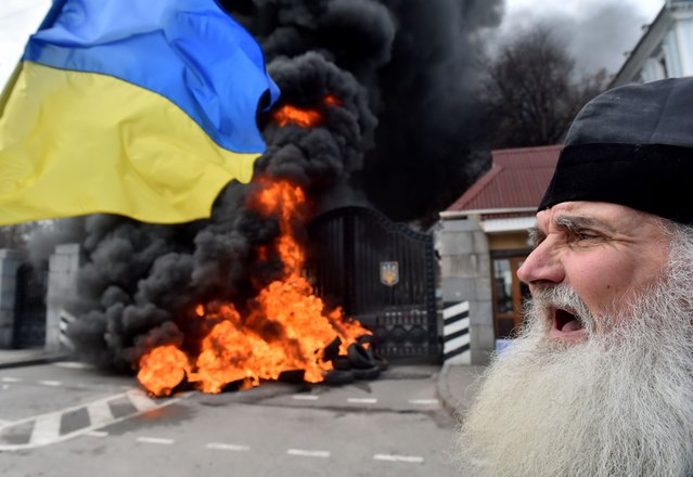 """An elderly Orthodox priest shouts as fighters of the """"Aydar"""" Ukrainian volunteer battalion, burn tyres at the entrance to the Ukrainian Defence Ministry in Kiev, on February 2, 2015 during an action to prevent the possible disbandment of their battalion. (Photo by Sergei Supinsky/AFP Photo)"""
