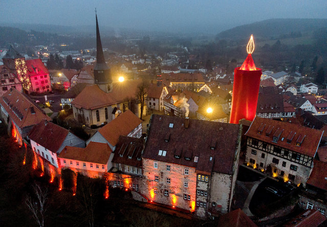 """One of the world's largest Christmas candles shines in the city of Schlitz, central Germany, Sunday, December 6, 2020. The candle consists of a historic stone tower wrapped in red cloth, with 110 light bulbs mounted at its tip to form a six-metre high """"flame"""". This brings the candle to a total height of 42 metres. (Photo by Michael Probst/AP Photo)"""