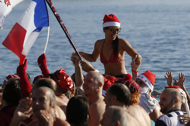 A woman wearing a swimsuit and a Christmas hat, attends, next to a French flag, the traditional Christmas bath on December 20, 2015 on the beach of the French riviera city of Nice, southeastern France. (Photo by Valery Hache/AFP Photo)