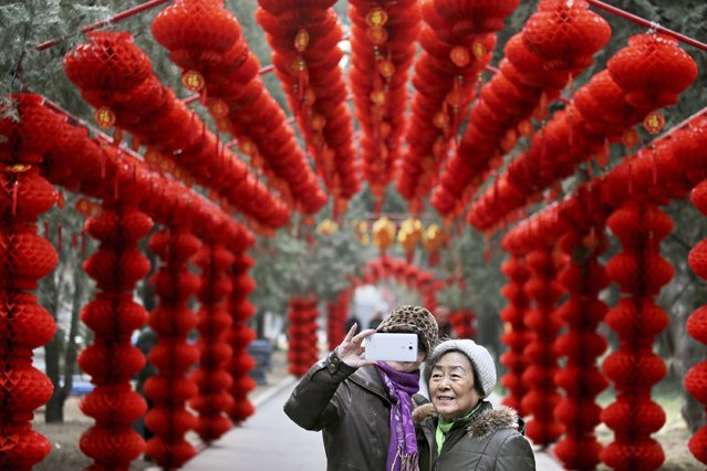 Visitors take a selfie in front of lantern decorations installed to prepare for Spring Festival celebrations in a temple fair at a park, in Beijing February 6, 2015. (Photo by Reuters/Stringer)