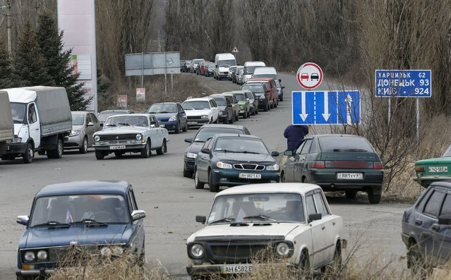 Cars queue to reach a border crossing point, before driving into Russian territory, outside the village of Uspenka, Donetsk region, February 8, 2015. (Photo by Maxim Shemetov/Reuters)
