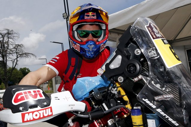 Honda motorcycle rider Joan Barreda Bort of Spain pushes his motorcycle as he leaves the technical verification area ahead of the Dakar Rally 2016 in Buenos Aires, Argentina, December 31, 2015. (Photo by Marcos Brindicci/Reuters)