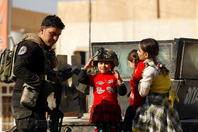 Children speak with a member of the Iraqi Special Operations Forces (ISOF) during a battle with Islamic State militants in Mosul, Iraq, November 28, 2016. (Photo by Khalid al Mousily/Reuters)