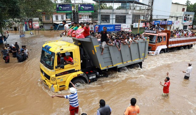 Indian passengers travel in a truck to a safer place as flood waters ravaged the National Highway 47 in Ernakulam district of Kochi, in the Indian state of Kerala, on August 17, 2018. Troop reinforcements stepped up desperate rescue attempts in India' s flood- stricken Kerala state on August 17 after more than 100 bodies were found in a day and a half, taking the crisis death toll to at least 164. (Photo by AFP Photo/Stringer)