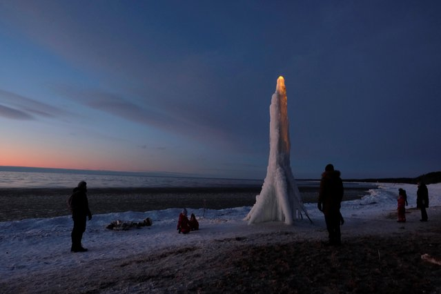 People gather next to an ice sculpture made by locals in the beach in Saulkrasti, Latvia on February 15, 2021. (Photo by Ints Kalnins/Reuters)
