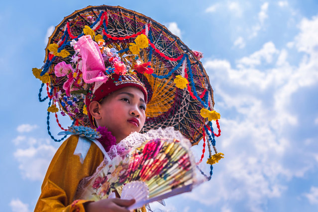 The young initiates also wear full face make up and guides accompany them with umbrellas to protect them from the sun's heat in Mae Hong Son, Thailand, April 2016. (Photo by Claudio Sieber/Barcroft Images)