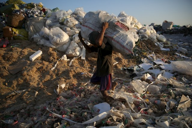A man carries a bag of recyclable waste at a rubbish dump outside Yangon January 7, 2016. (Photo by Soe Zeya Tun/Reuters)