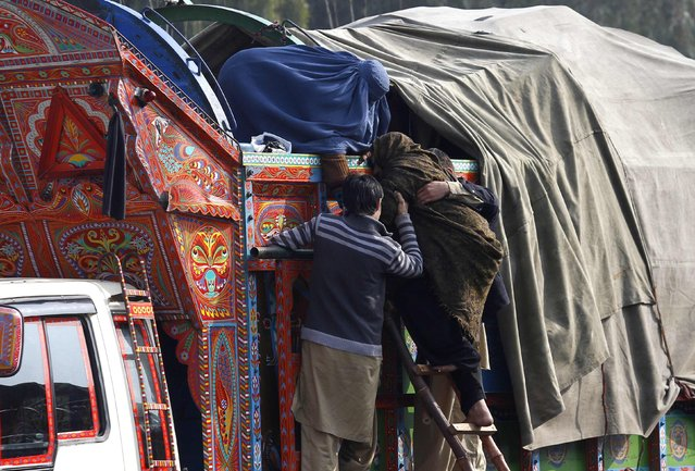 An elderly Afghan refugee woman is helped by family members to board a truck as they prepare to go back to Afghanistan with others, at the United Nations High Commissioner for Refugees (UNHCR) office on the outskirts of Peshawar February 18, 2015. (Photo by Fayaz Aziz/Reuters)