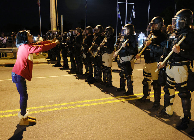 Patrice Revelle stands in front of police in riot gear as they force people off a street as they protest the killing of Andrew Brown Jr. on April 27, 2021 in Elizabeth City, North Carolina. The police were enforcing an 8 pm curfew announced after the shooting death of Brown by Pasquotank County Sheriff deputies on April 21. (Photo by Joe Raedle/Getty Images)