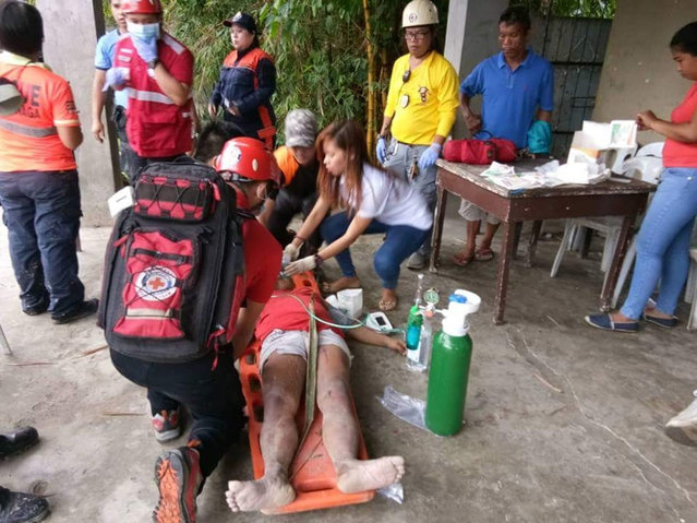 In this handout photo provided by Philippine Red Cross-Cebu Chapter, Red Cross volunteers treat a victim after she was pulled out of her house that was struck by a landslide in Naga city, Cebu province central Philippines on Thursday, September 20, 2018. A Philippine official says several people were killed and more are feared buried in a landslide that hit two villages amid heavy rains in the central Philippines. (Photo by Philippine Red Cros/Cebu Chapter via AP Photo)