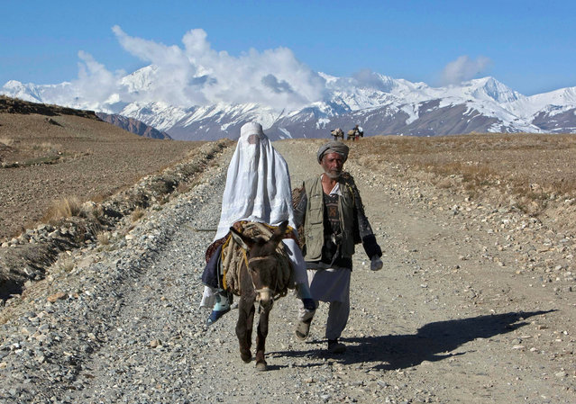 An Afghan woman, wearing a burqa, rides on a donkey alongside her husband in the Ishkashim district of Badakhshan province, north east of Kabul April 24, 2008. (Photo by Ahmad Masood/Reuters)