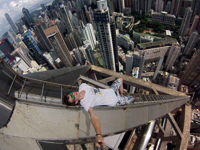 Alexander Remnov uses to selfie stick to capture a unique view of the Hong Kong skyline. (Photo by Alexander Remnov/Caters News Agency)