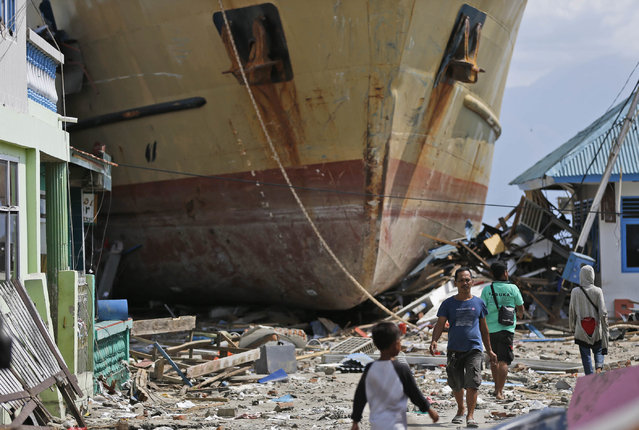 In this Thursday, October 4, 2018, photo, men walk past Sabuk Nusantara 39 which was swept ashore by the tsunami in Wani village on the outskirt of Palu, Central Sulawesi, Indonesia. The crew of the hulking ferry dropped by the tsunami in front of a row of houses in an Indonesian village say the wave that drove them onto land was a towering 10-15 meters or higher and came just several minutes after a quake made the ship bounce like a basketball. (Photo by Dita Alangkara/AP Photo)