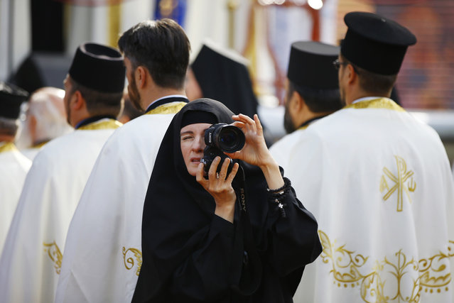 A nun takes pictures as believers mark 1,700 years since the Edict of Milan, when Roman emperor Constantine issued instructions to end the persecution of Christians, in the southern Serbian city of Nis October 6, 2013. Nis, some 220 km (137 miles) south of Belgrade, is the birthplace of Constantine the Great, the first Roman emperor to convert to Christianity. The Edict of Milan, which he had a part in enacting, proclaimed official tolerance of Christianity across the Empire. (Photo by Marko Djurica/Reuters)