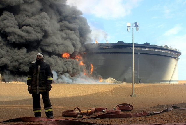 A Libyan fireman stands in front of smoke and flames rising from an oil storage tank at an oil facility in northern Libya's Ras Lanouf region on January 23, 2016, after it was set ablaze earlier in the week following attacks launched by Islamic State (IS) group jihadists to seize key port terminals. (Photo by AFP Photo/Stringer)