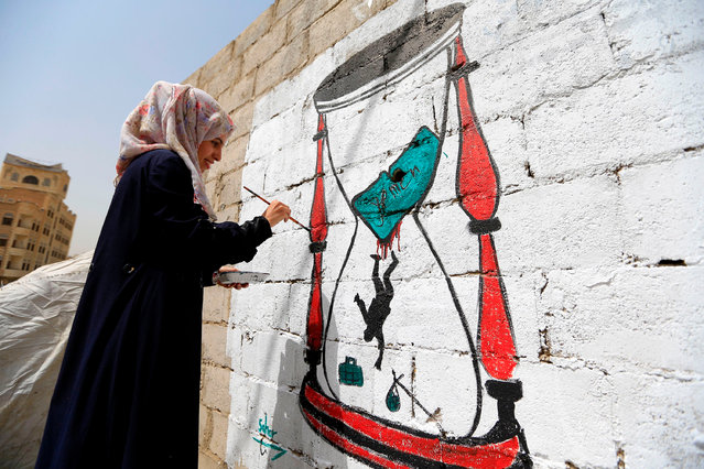 A Yemeni artist paints a pro- peace graffiti on a wall in the capital Sanaa on August 16, 2018, as they call for peace and tolerance and rejecting the ongoing conflict in the Arab country. (Photo by Mohammed Huwais/AFP Photo)