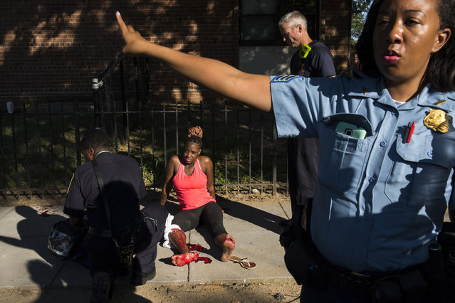 Officers with the Metropolitan Police Department's 6th District work a shooting scene in northeast Washington DC on August 27, 2016. A  woman, center, was shot in her right leg at the Kenilworth Parkside apartment complex. Police recruitment numbers are down in the District and departments throughout the country. (Photo by Michael Robinson Chavez/The Washington Post)