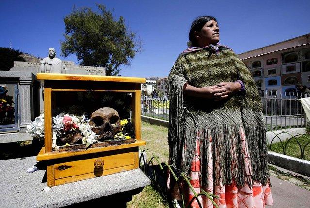 "A woman stands next to a skull during the ""Dia de los natitas"" ceremony. (Photo by David Mercado/Reuters)"
