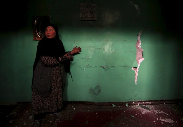 An Afghan woman shows a damaged wall of a shrine after a suicide attack in Kabul March 25, 2015. (Photo by Omar Sobhani/Reuters)