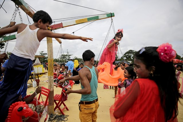 In this August 23, 2018, photo, a Rohingya refugee child rides a merry-go-round at Kutupalong refugee camp in Bangladesh. More than half a million Rohingya children live in the congested camps. They rely on 1,200 learning centers set up by aid organizations that can't accommodate everyone and only offer classes up to a 5th-grade level. Most Rohingya girls are expected to get married by the age of 16, and sometimes as early as 14. (Photo by Altaf Qadri/AP Photo)