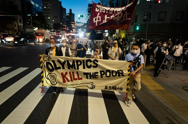 Protesters march to protest against holding the Tokyo 2020 Summer Olympic Games in Tokyo on Friday, July 16, 2021. (Photo by Hiro Komae/AP Photo)