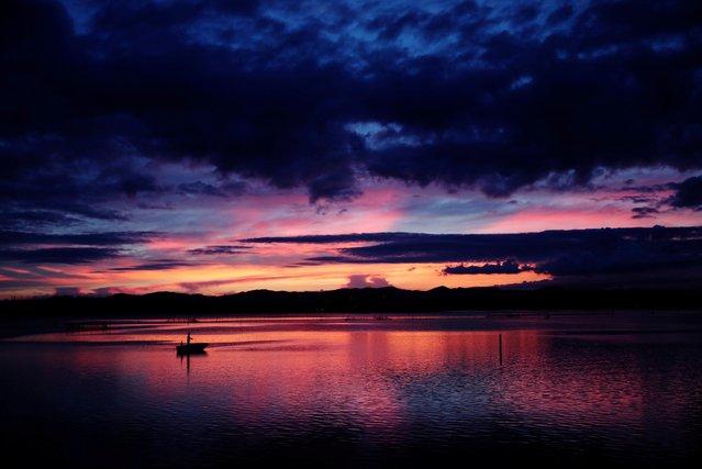 A man fishes on a boat at Lake Hamana in the sun set in Hamamatsu, Shizuoka Prefecture, Japan on July 15, 2021. (Photo by Kim Kyung-Hoon/Reuters)