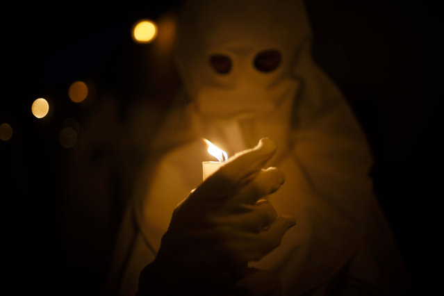 "A penitent holds a candle as he takes part in ""Nuestro Senor Atado a la Columna, Maria Santisima de la Paz y San Juan Evangelista"" Holy Week procession in Arcos de la Frontera, Spain, Tuesday, March 31, 2015. (Photo by Daniel Ochoa de Olza/AP Photo)"