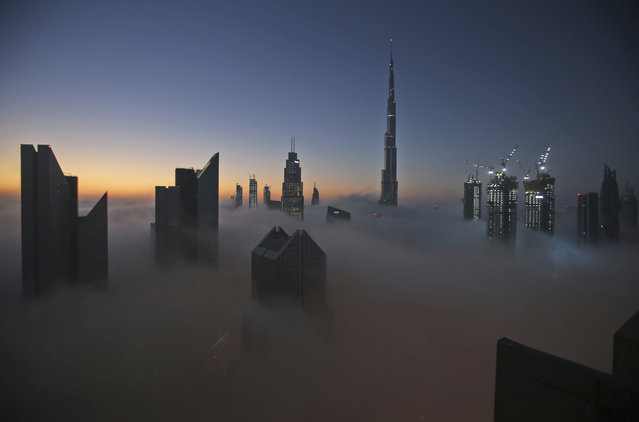 The sun rises over the city skyline with the Burj Khalifa, world's tallest building at the backdrop, seen from a balcony on the 42nd floor of a hotel on a foggy day in Dubai, United Arab Emirates, Saturday, December 31, 2016. A thick fog has shrouded downtown Dubai ahead of a New Year's Eve fireworks display at the world's tallest building. (Photo by Kamran Jebreili/AP Photo)