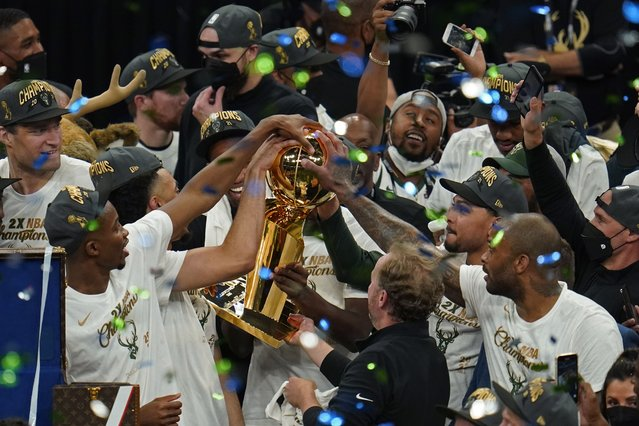 The Milwaukee Bucks celebrate with the championship trophy after defeating the Phoenix Suns in Game 6 of basketball's NBA Finals in Milwaukee, Tuesday, July 20, 2021. The Bucks won 105-98. (Photo by Paul Sancya/AP Photo)