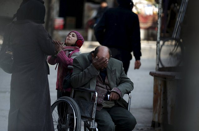 A girl asks a passerby for help to pay a medical bill as her father sits in his wheelchair in the Douma neighbourhood of Damascus Syria February 3, 2016. (Photo by Bassam Khabieh/Reuters)