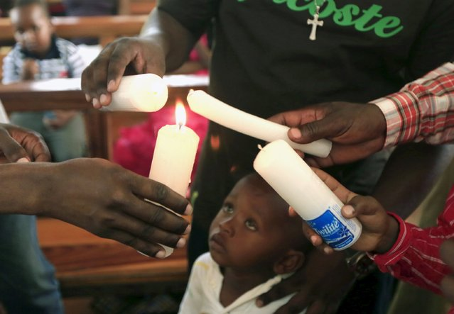 A boy looks on as church members light candles during an Easter Sunday service at the Catholic church in Garissa April 5, 2015. (Photo by Noor Khamis/Reuters)