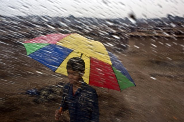 An Afghan refugee holds an umbrella during a rainstorm, in a slum on the outskirts of Islamabad, Pakistan, Saturday, February 7, 2015. (Photo by Muhammed Muheisen/AP Photo)
