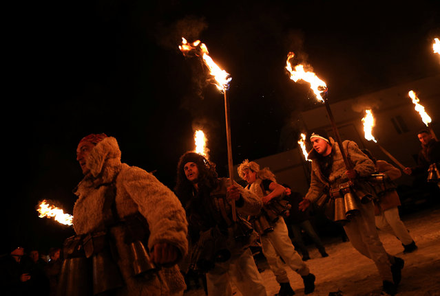 """Men dressed in costumes made of animal fur called """"kuker"""" carry torches during a festival in the town of Batanovtsi, Bulgaria January 13, 2017. (Photo by Stoyan Nenov/Reuters)"""