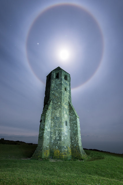 A picture of the moon surrounded by a halo of light on February 02, 2015 in Isle Of Wight, England. Jupiter is the brightest star on the left side of the halo. Isle of Wight based amateur photographer Ainsley Bennett captured this beautiful shot of the moon producing a strong halo at around midnight. The rings can be clearly seen in the high stratus clouds. Jupiter can be seen shining brightly to the left of the moon. (Photo by Ainsley Bennett/Barcroft Media)